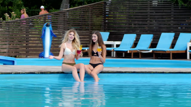Beautiful-girlfriends-With-beverage-in-arms-relaxing-in-pool-outdoor-Summer-vacation-of-Young-friends-at-resort