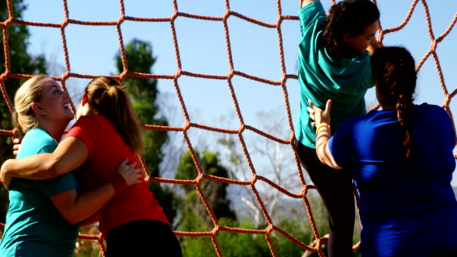 Women-practicing-net-climbing-during-obstacle-course