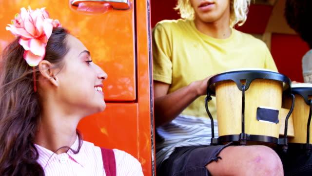 Amigos-tocando-tambor-y-guitarra-junto-a-la-caravana-en-el-Parque-4k