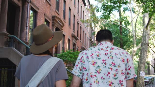 Rückansicht-des-Paares-zu-Fuß-entlang-der-Urban-Street-In-New-York-City