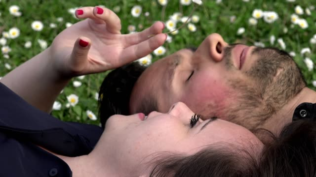 sweet-and-romantic-couple-lying-on-the-grass-chatting