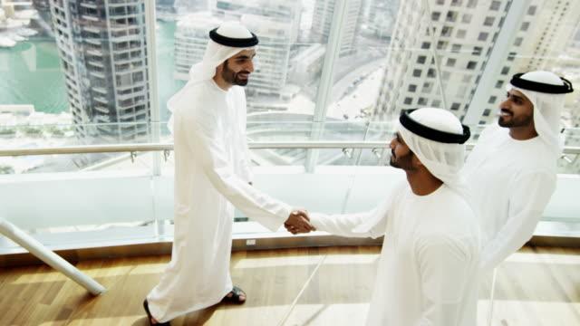 Arab-males-in-national-dress-handshake-greeting-downtown