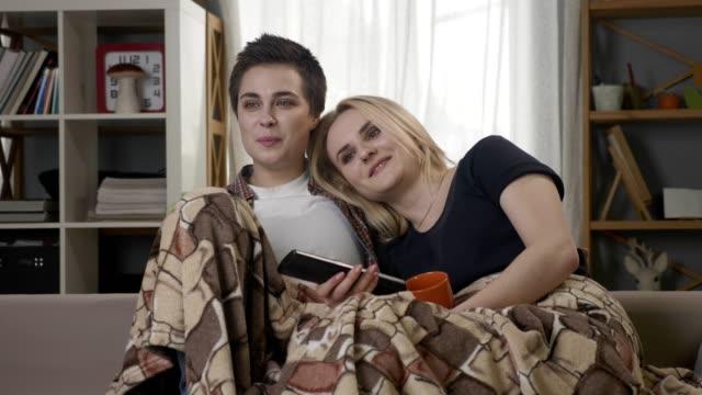 Zwei-junge-lesbische-Mädchen-sitzen-auf-der-Couch-bedeckt-mit-einer-warmen-Decke-hält-Becher-in-der-Hand-dunklen-Tee-trinken-Kaffee-kuscheln-Fernsehen-Kanal-Ausführung-Lachen-60fps