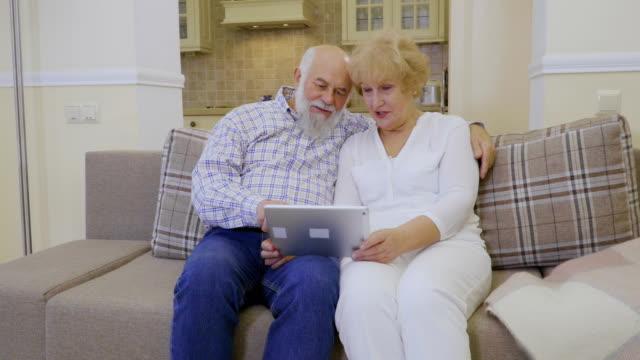 Mujer-Senior-y-senior-hombre-utiliza-pastilla-relajante-en-el-sofá-en-casa