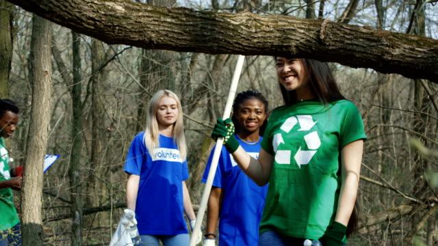 Diverse-volunteers-walking-in-forest