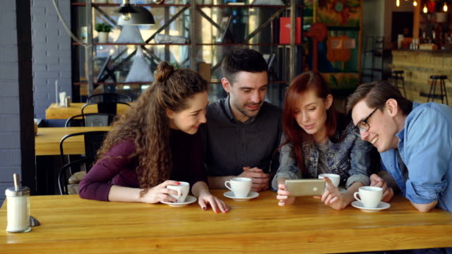 Good-looking-friends-are-watching-interesting-video-and-discussing-it-while-drinking-tea-at-table-in-cozy-cafe-Modern-lifestyle-and-happy-people-concept-