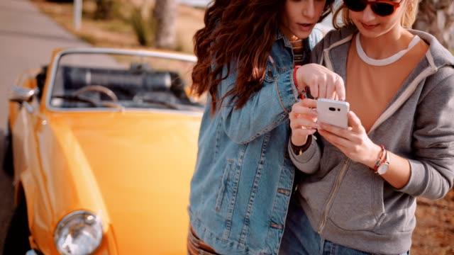 Frauen-mit-Smartphone-und-lesen-Onlinekarte-Road-trip