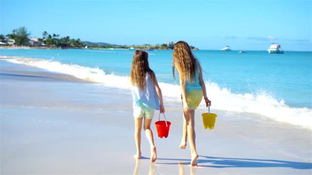Adorables-niñas-caminando-por-la-playa-y-divertirse-juntos