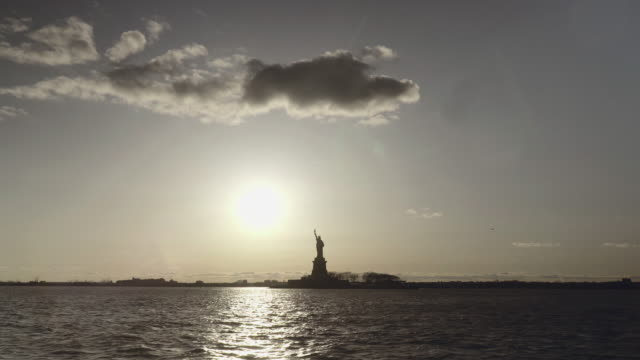 Extra-wide-shot-of-Statue-of-Liberty-filmed-in-the-sunset-from-the-river-in-New-York-United-States-of-America