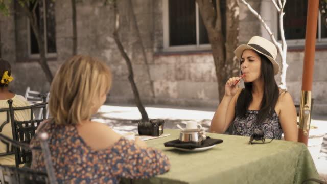 Female-Friends-At-Bar-Drinking-Coffee-Smoking-E-Cig