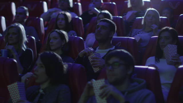 Group-of-people-are-laughing-while-watching-a-comedy-film-screening-in-a-movie-cinema-theater-