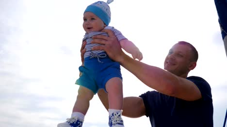 daddy-raised-baby-in-arms-little-kid-in-father-s-strong-hands-in-sunlight-child-into-hands-of-dad-on-blue-sky-background