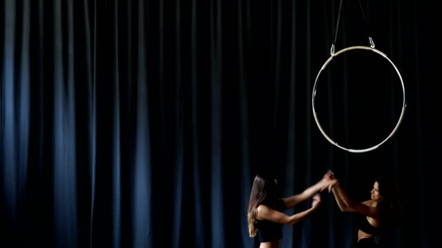 Two-professional-gymnasts-are-gesturing-hands-at-the-dark-curtain-background