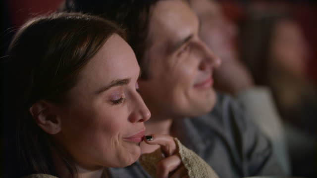 Young-couple-enjoying-film-in-cinema-embracing-Love-couple-watching-movie