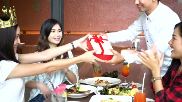 Young-Asian-couple-giving-a-present-gift-box-and-friends-clapping-hands-nearby-at-restaurant