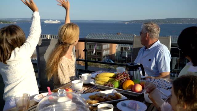 Una-gran-familia-feliz-cena-en-la-terraza-abierta-y-agita-sus-manos-pasando-por-el-ferry-mar