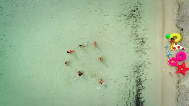 Aerial-view-of-friends-playing-volleyball-standing-in-sea-by-sandy-beach-