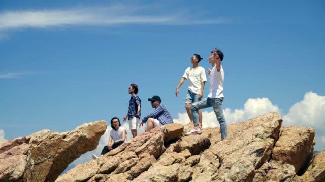 Asia-adultos-jóvenes-de-pie-en-la-cima-de-las-rocas-por-el-mar