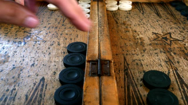 Two-young-men-playing-backgammon-on-a-wooden-table-rolling-dices-and-move-the-piece-