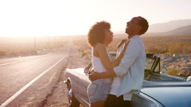Junges-Paar-stützte-sich-auf-ihr-Auto-am-Straßenrand-umarmen