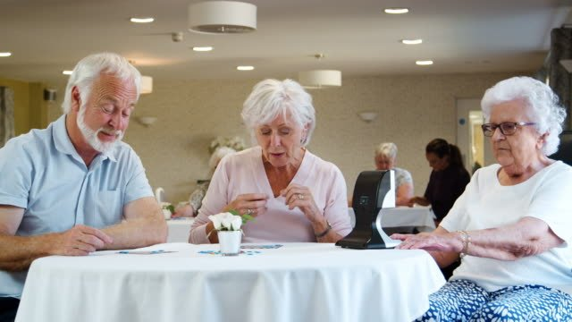 Group-Of-Seniors-Playing-Game-Of-Bingo-In-Retirement-Home