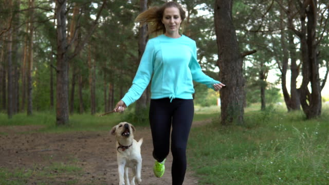 Young-woman-is-walking-with-dog-in-the-forest