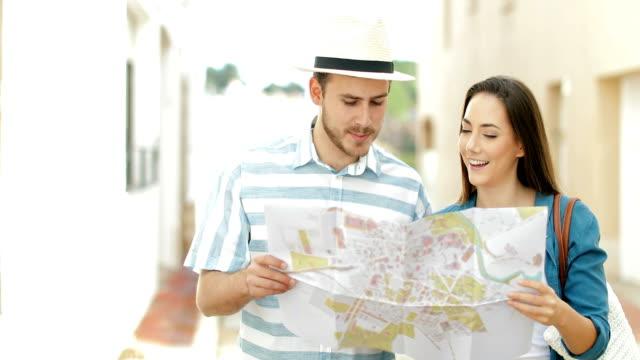 Pareja-de-turistas-caminando-comprobación-de-mapa-en-una-calle-de-la-ciudad