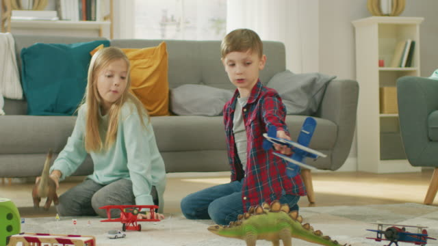 In-the-Living-Room:-Boy-and-Girl-Playing-with-Toy-Airplanes-and-Dinosaurs-while-Sitting-on-a-Carpet-Sunny-Living-Room-with-Children-Having-Fun-