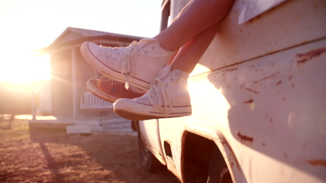 Teen-couple-s-legs-hanging-out-of-vehicle-with-sun-flare