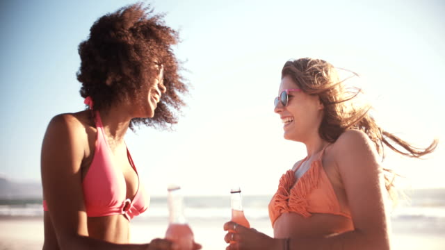 Girl-friends-in-bikinis-talking-on-a-beach-with-alcopops