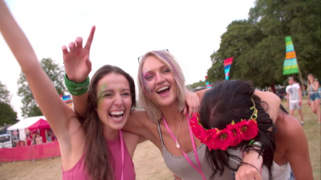 Three-young-female-friends-having-fun-at-a-music-festival