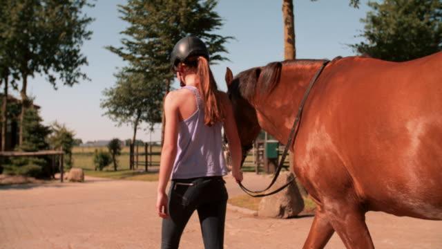 Girl-a-escasos-pasos-de-distancia-con-su-caballo-en-un-patio-al-aire-libre