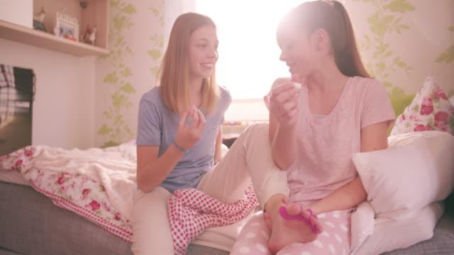 Teenager-Freunden-teilen-Nagellack-in-einem-farbenfrohen-Schlafzimmer