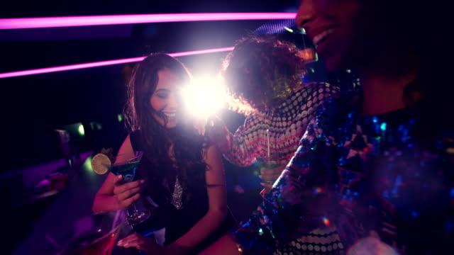 Multi-ethnic-friends-joyful-smiling-while-chatting-in-club