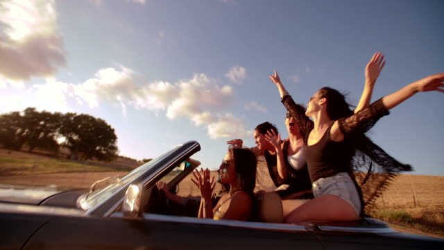 Teenager-friendspulling-faces-to-the-camera-on-road-trip