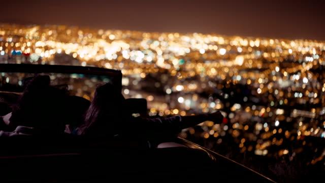 Eine-Gruppe-von-Freunden-sitzen-in-einem-retro-Cabrio-Auto-bei-Nacht
