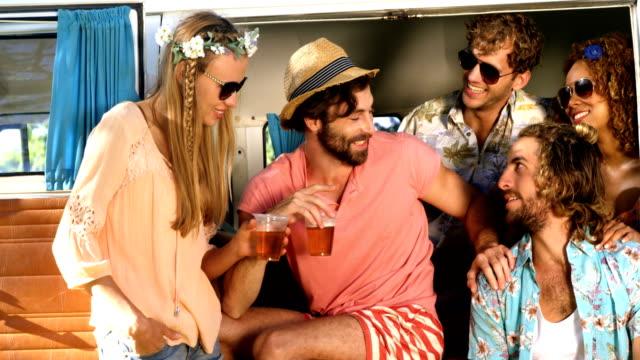 Gruppe-von-Freunden-ein-Bier-trinken-und-sitzen-auf-dem-Wagen