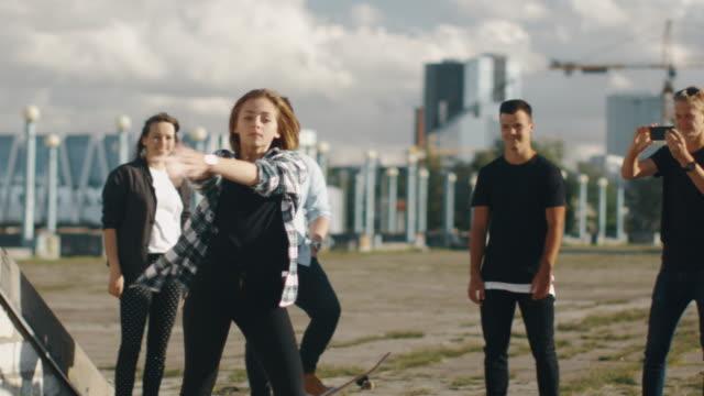 Niña-adolescente-realizando-danza-moderna-para-grupo-de-amigos-al-aire-libre-en-entorno-urbano-