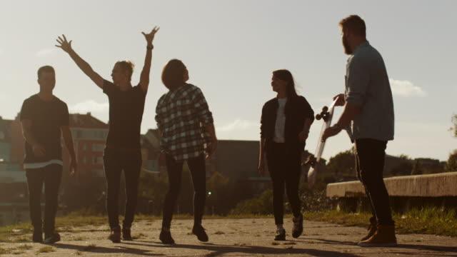 Grupo-de-adolescentes-felices-riéndose-levantando-las-manos-saltar-mientras-se-mueve-hacia-adelante-a-la-cámara-