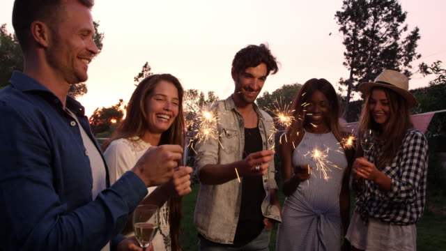 Group-Of-Friends-With-Sparklers-Enjoying-Outdoor-Party