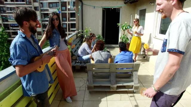 Mann-spielt-Ukulele-während-er-mit-Freunden-auf-dem-Dach-hängt