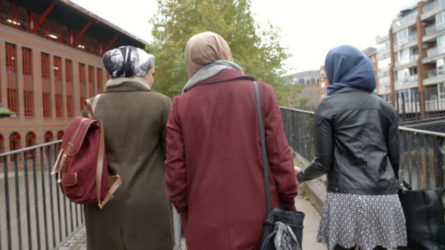 Rear-View-Of-British-Muslim-Female-Friends-Walking-In-City