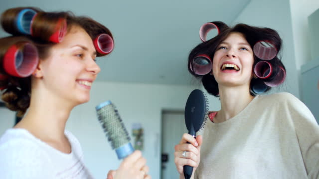 Two-funny-girls-singing-with-combs-dance-and-have-joy-in-living-room-at-home