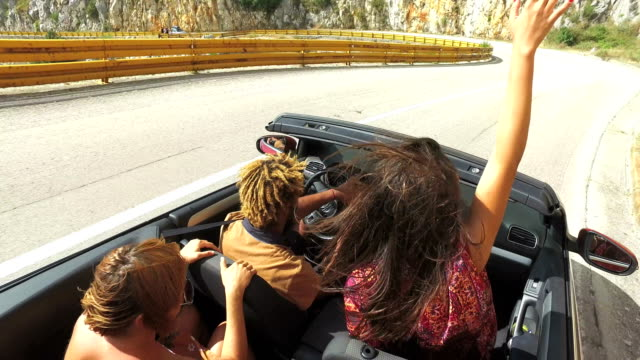 Group-of-friends-driving-on-the-road-along-the-coast-in-red-convertible