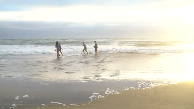 Friends-at-beach-playing-in-surf