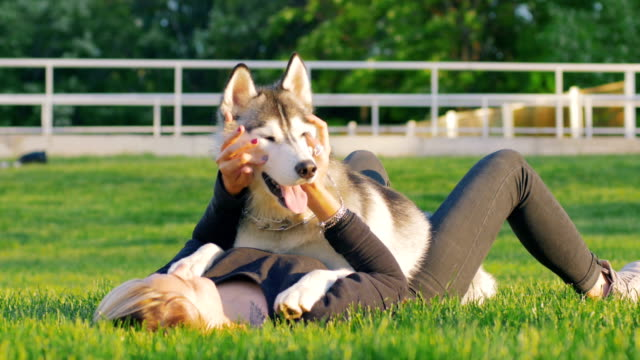 Beautiful-young-woman-playing-with-funny-husky-dog-outdoors-in-park