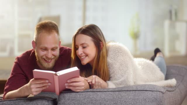 Pareja-dulce-joven-tumbado-en-un-sillón-y-leer-un-libro-divertido