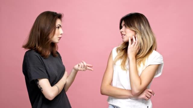 Chica-guapa-joven-sugiriendo-ideas-para-su-amiga-seguro-dudando-aislado-sobre-fondo-rosa