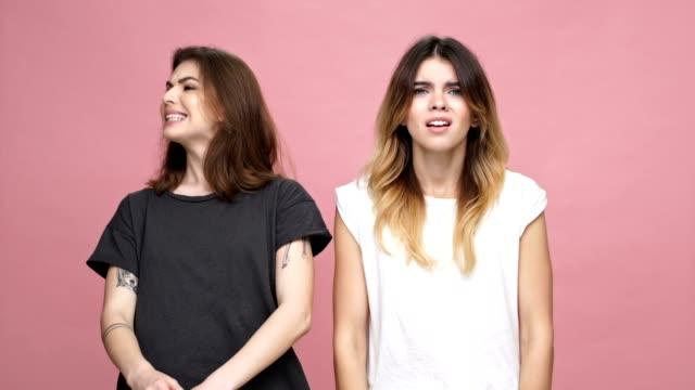 Dos-jóvenes-indignan-mujeres-con-los-brazos-doblados-y-mirando-a-cámara-aislada-sobre-fondo-rosa