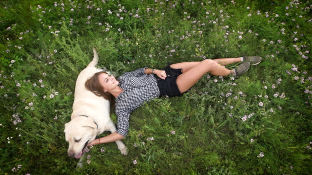 Funny-woman-lay-on-the-grass-and-plays-with-the-dog